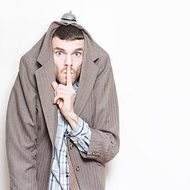 Undercover agent hiding under jacket with hospitality bell on head